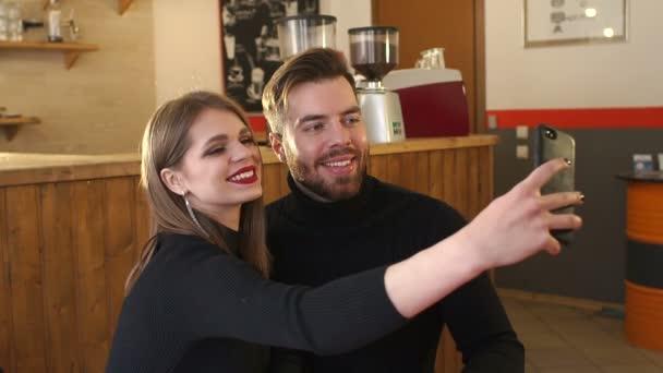 Portré pár egy kávézóban, akkor megteszi a selfie és élvezze az illatos cappuccino