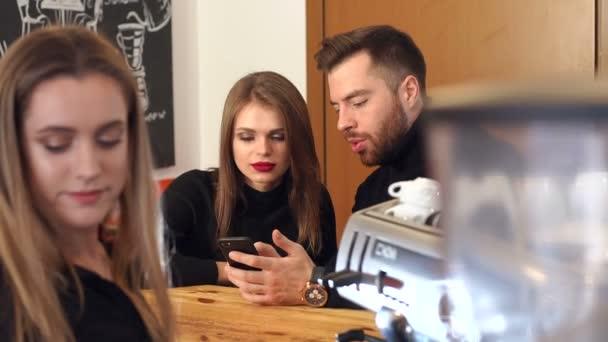 Egy pár pihenő egy kávézóban, ezek a gazdaság telefonok, várva a kávé.