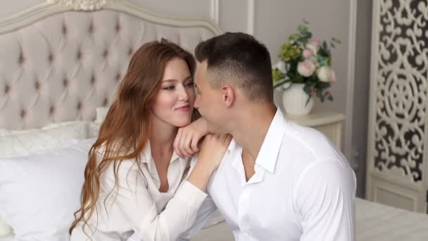 Portrait of beautiful romantic couple in white shirts in the bedroom on the bed