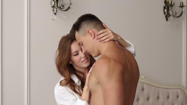 ein liebendes Paar umarmt sich, während es in einem schönen modernen Schlafzimmer steht.