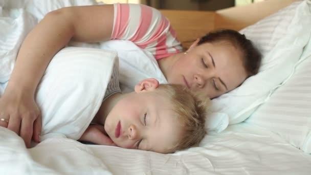 Zblízka matka něžně objala svého spícího syna v posteli.