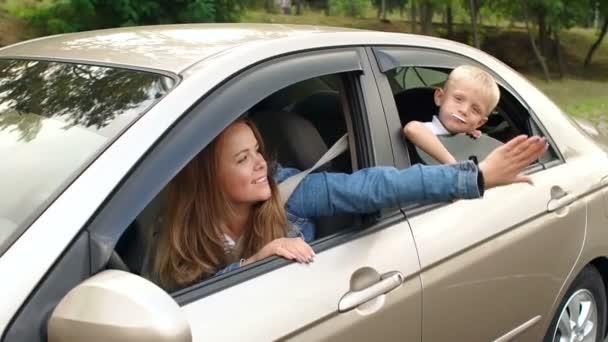 glückliche Mutter und Sohn, die während der Fahrt Spaß im Auto haben. Zeitlupe.