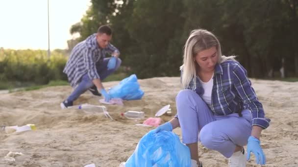 Gruppe junger Freiwilliger sammelt Müll am Strand ein.