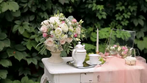 Arredamento da sposa con tavolo antico, fiori e velo.