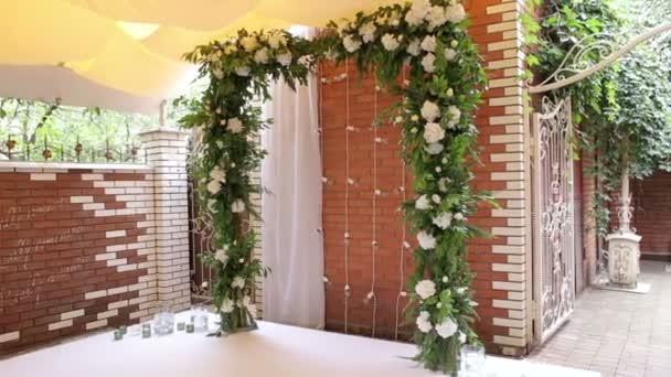 Arco di nozze con fiori bianchi contro un muro di mattoni.
