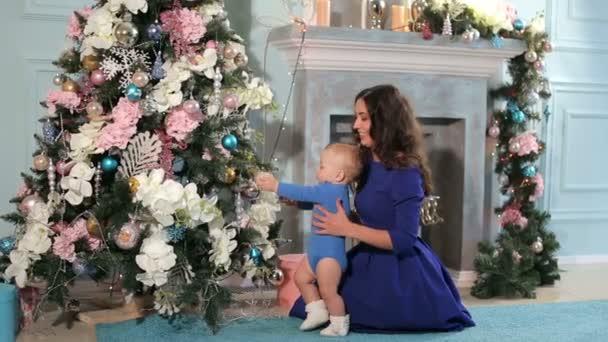 Glückliche Mutter und kleiner Sohn spielen an Weihnachten zu Hause.