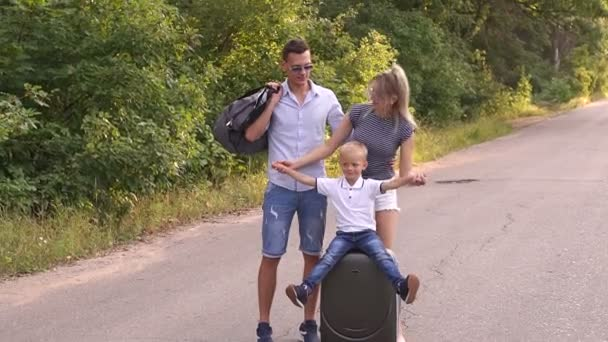 Portrét šťastné rodiny s mladým synem na silnici v lese s kufry
