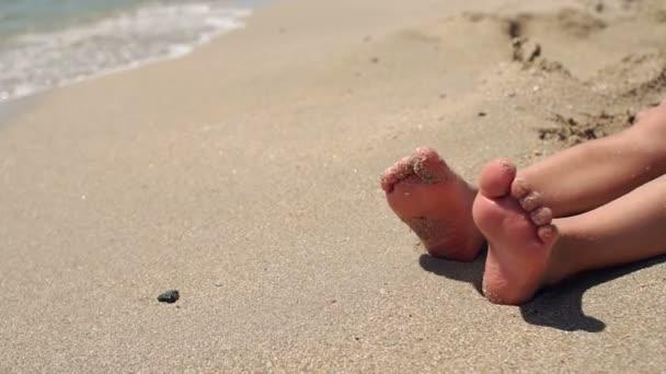 Közeli fel a lábát egy kis gyerek a tengerparton a homokban lassított mozgás.