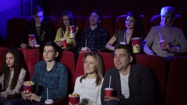 Fiatal vicces tinédzserek vicces filmeket néznek a moziban, popcornt esznek.