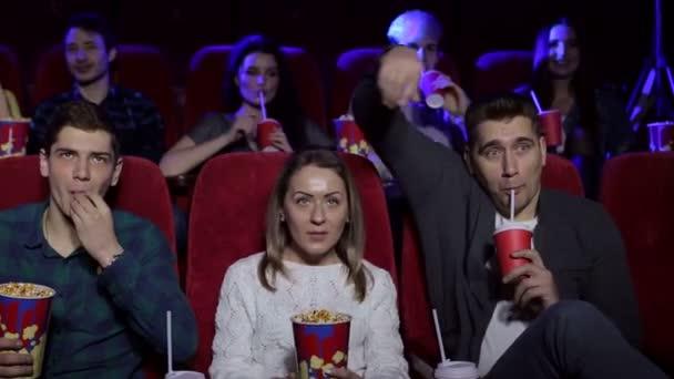 Fiatal emberek ülnek a moziban, néz egy film és étkezési pop kukorica.