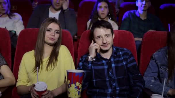 Böser Mann telefoniert im Kino und stört Besucher.