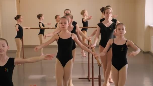 Baleríny současně ukazují choreografické cvičení v baletní třídě.
