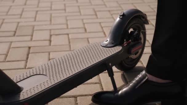 Detailní záběr na podnikatele nohy na elektrickém skútru v parku.