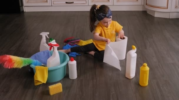 Ein kleines Mädchen spielt zu Hause mit Papierhandtüchern auf dem Küchenboden.