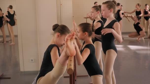 Skupina baletek dívky dělat strečink cvičení před taneční lekce.