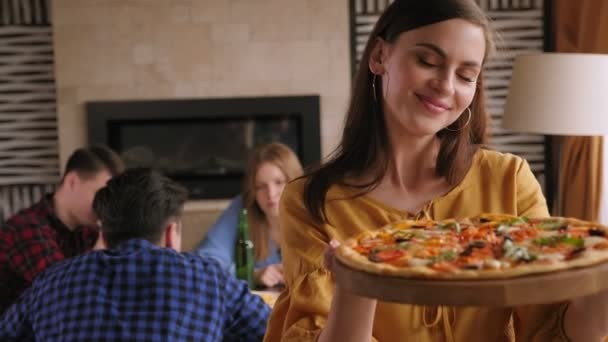 Portrét dívky s pizzou v rukou v pizzerii, dívá se do kamery