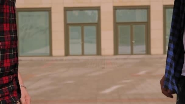 Detailní záběr dvou přátel potřásajících si rukou ve městě poblíž moderní budovy.