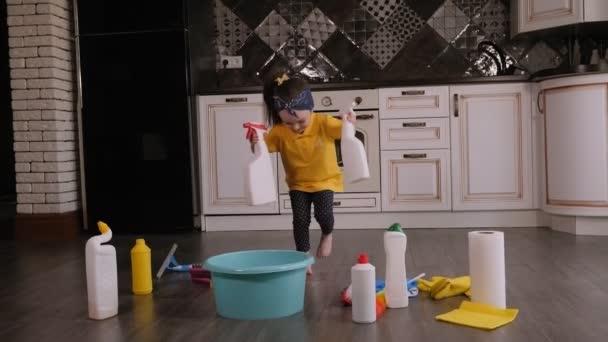 Portrét veselého děvčátka v kuchyni mezi pracími prostředky. Úklid domu