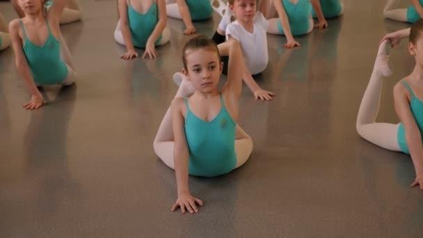 A fiatal táncosok torna gyakorlatokat végeznek a bemelegítés alatt az osztályteremben..