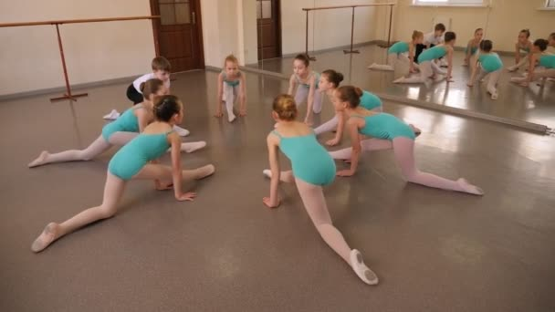Little ballet dancers sitting on split and stretching out before performance.
