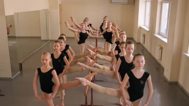 Fiatal balerinák próbája egy balett iskolában a balett korlát közelében.