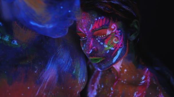Portrét páru s UV kresbami na kůži ve světle zářivek