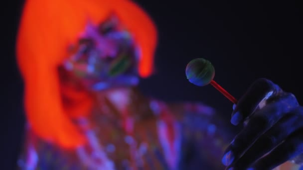Girl with UV drawings on her body with a Lollipop in neon light in the dark.