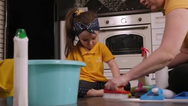Cheerful mother and little daughter clean the house together and have fun.