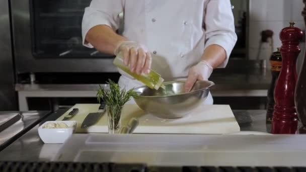 Detailní záběr kuchaře, jak nalévá olivový olej na talíř v kuchyni v restauraci.