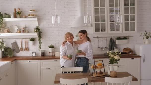 An adult mother and daughter hugging in the kitchen, they drink tea and talk.