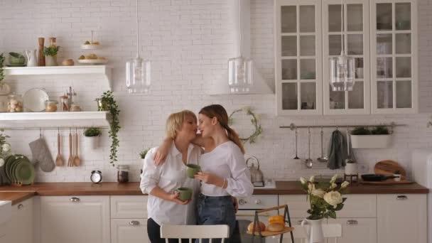 Egy felnőtt anya és lánya ölelkeznek a konyhában, teát isznak és beszélgetnek..