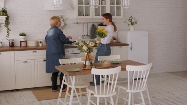Young woman runs to an elderly mother and gives her a bouquet of tulips at home
