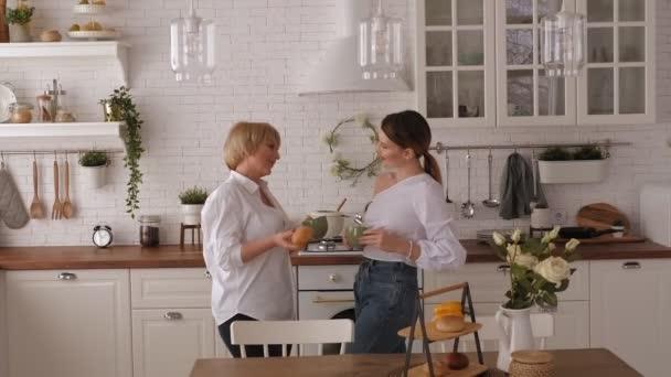 Usmívající se starší a mladé ženy si užívají čas doma, popíjejí spolu čaj.
