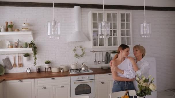 Portrét starší matky se svou milovanou dcerou doma v kuchyni