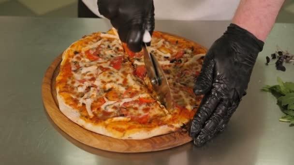 Šéfkuchař krájení pizzy s kulatým nožem v kuchyni restaurace před podáváním