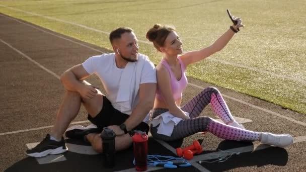 Pár vezme selfie na svůj telefon, zatímco sedí na běžícím pásu na stadionu