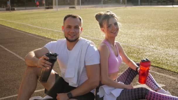 Pár sedí na běžeckém pásu na stadionu s lahvemi vody a palec nahoru