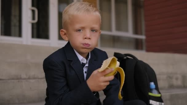 Egy kisiskolás banánt eszik az iskola lépcsőjén ebéd közben..
