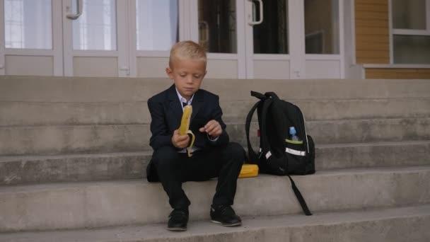 Iskolásfiú ül a lépcsőn az iskolában, és eszik egy banánt, mellette egy hátizsák