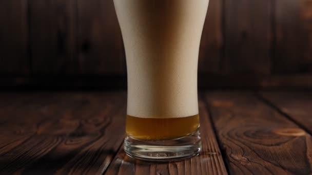 Sklenice lehkého piva se spoustou pěny a bublinek na dřevěném pozadí.