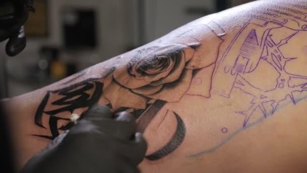 Szakmai tetováló művész, amely tetoválás a lábát egy fiatal lány.