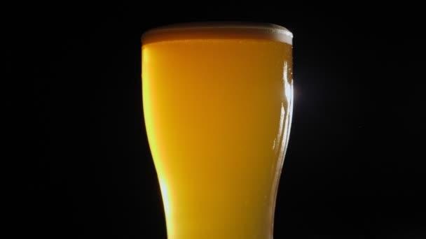 Egy közeli, friss habos sör egy pohárban, fekete háttérrel. Lassú mozgás..