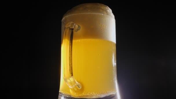 Hrnek lehkého piva s pěnou se pomalu otáčí na černém pozadí.