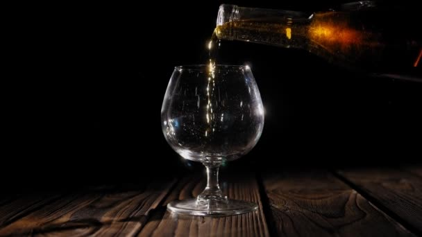 A csapos nagy borospohárba önti a konyakot a bárpultra..