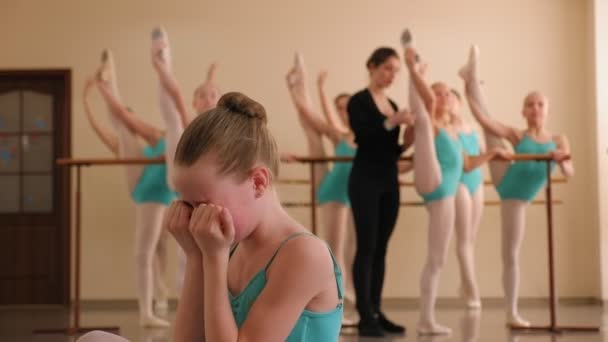 A little ballerina is crying in a ballet dance studio.