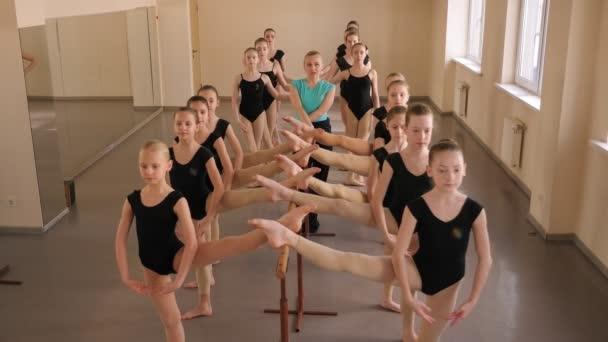 A female choreographer teaches children ballet at a classical dance school.