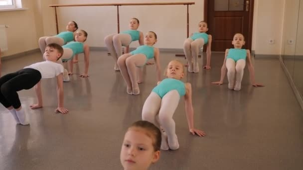 Group of ballet girls doing stretching exercises before dance lessons.