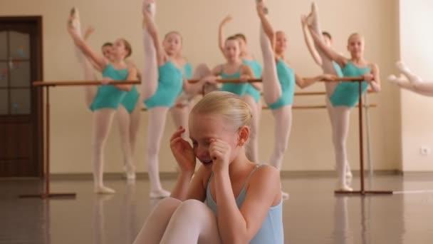 Közelkép egy feldúlt kislányról a balett stúdióban, sír..