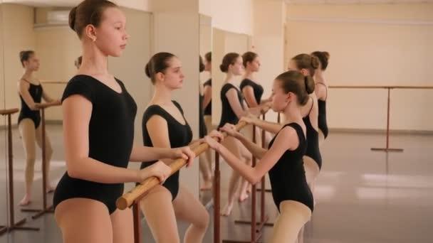 Gruppe von Ballettmädchen macht Dehnübungen vor dem Tanzunterricht.