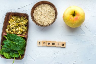 Spinach, pumpkin seeds, sesame, apple on a white background. Anemia concept. Close-up